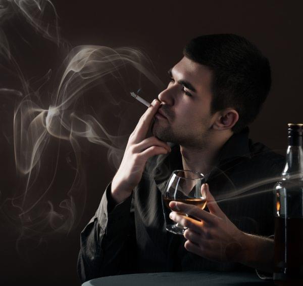 Man Smoking While Drinking Alcohol