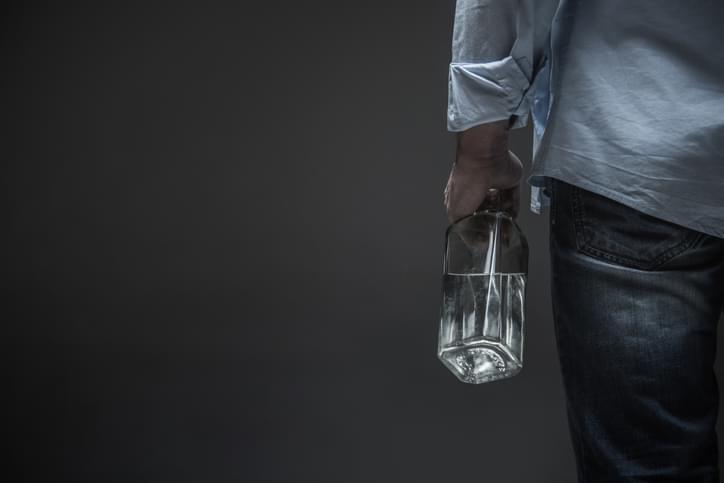 Male holding empty bottle of alcohol